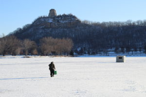 A picture of Sugar Loaf Bluff with a frozen lake in the foreground. An ice fisherman walks to his shelter in the foreground.